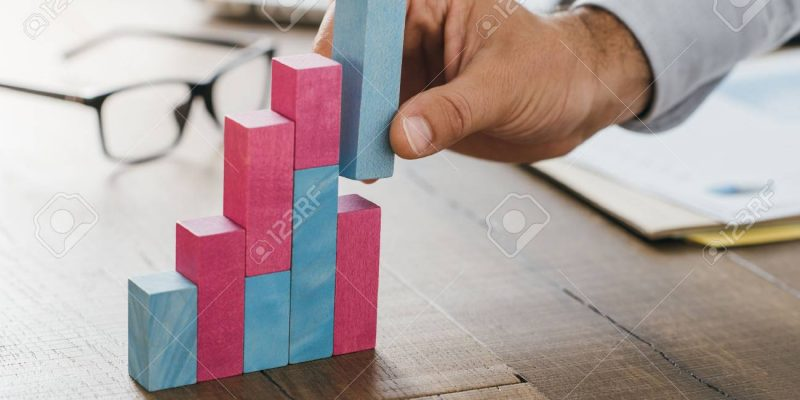 82811764-businessman-working-at-office-desk-he-is-building-a-growing-financial-graph-using-wooden-toy-blocks-